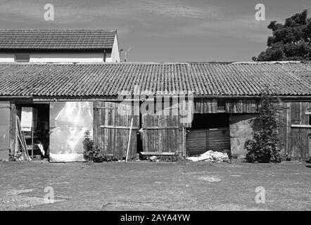 monochrome image of patched and repaired scruffy rural workshop outbuildings with shabby broken door - Stock Photo