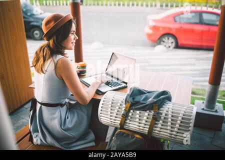 Beautiful young caucasian woman sitting on a terrace in a cafe in summer at a wooden table in a hat and a plate uses technology,