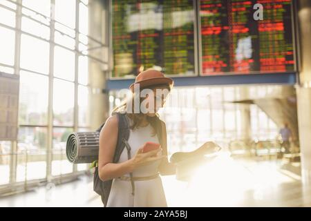 theme travel and transportation. Beautiful young caucasian woman in dress and backpack standing inside train station terminal lo - Stock Photo
