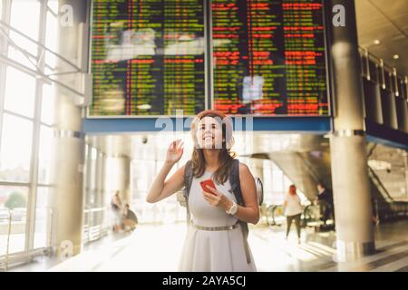 Theme travel and tranosport. Beautiful young caucasian woman in dress and backpack standing inside train station or terminal loo