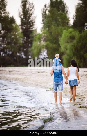 Family holiday near the sea. Two adults in jeans clothes with a child in their arms walk along the sandy beach from behind - Stock Photo