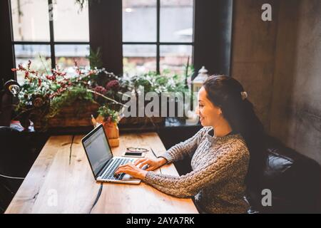 beautiful young brunette woman using a laptop at coffee shop at a wooden table near window typing text on a keyboard. In winter, - Stock Photo