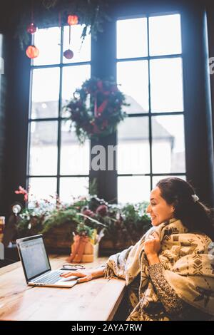 beautiful young girl uses laptop technology, types text looking at the monitor in a cafe by the window at wooden table, in winte - Stock Photo