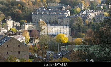 panoramic view of the town of hebden bridge in west yorkshire with streets of stone houses on steep hills in autumn sunlight sur - Stock Photo