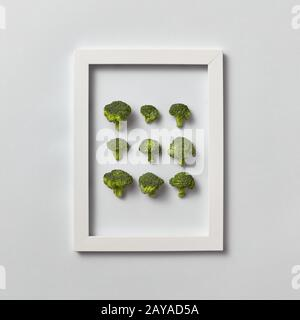 Fresh organic broccoli set in a frame on a light gray background. - Stock Photo