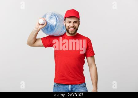 Delivery Concept: Portrait of smiling bottled water delivery courier in red t-shirt and cap carrying tank of fresh drink isolate - Stock Photo