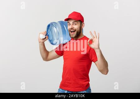 Portrait smiling bottled water delivery courier in red t-shirt and cap carrying tank of fresh drink and showing ok isolated over - Stock Photo