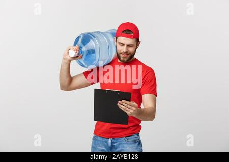 Portrait smiling bottled water delivery courier in red t-shirt and cap carrying tank of fresh drink and showing thumb up isolate - Stock Photo