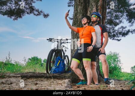 Happy couple with mountain bike taking selfie smartphone outdoors. A happy couple, who lead an active lifestyle, stopped in the - Stock Photo