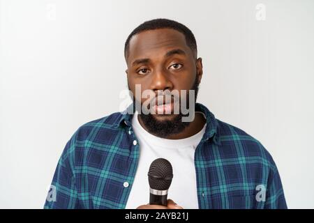 young handsome african american boy singing emotional with microphone isolated on white background. - Stock Photo