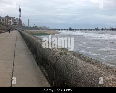 a view of blackpool promenade in winter with stormy sea tower and central pier with unidentifiable people walking along the seaf - Stock Photo
