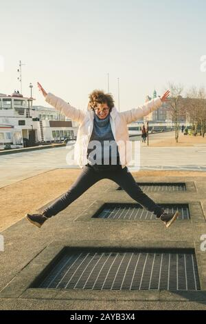 adult person rejoices like child. Playground trampoline in ground, children trampoline, springs throws people up fun and cool. C Stock Photo