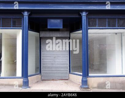 the facade of an old abandoned shop painted blue and white with empty store front dirty windows and closed shutters on the door - Stock Photo