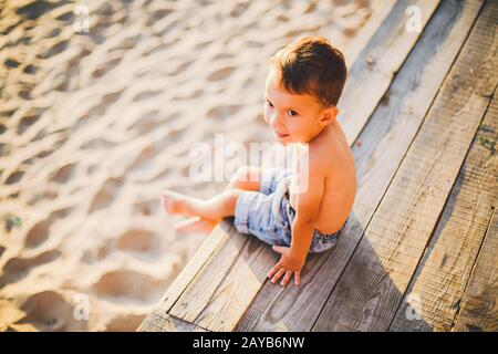 Little Caucasian boy child sitting on wooden pier sandy beach, summer time, sea vacation near water. The theme is the flow of ti Stock Photo