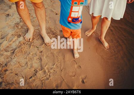 Happy family on the beach. Closeup of family feet with boy baby walking on sand. Man and woman holding their baby. Walk by the r