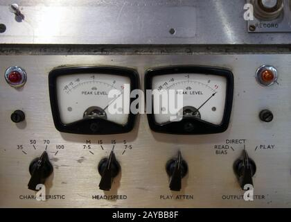 a close up of two old decibel meters on an old vintage reel to reel tape recorder with control knobs and switches - Stock Photo