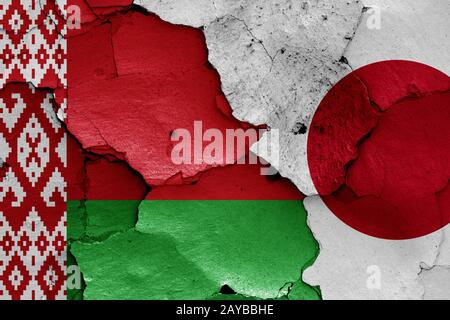 flags of Belarus and Japan painted on cracked wall - Stock Photo
