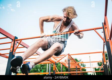 strong athlete doing pull-up on horizontal bar. Muscular man doing pull ups on horizontal bar in park. Gymnastic Bar During Work - Stock Photo