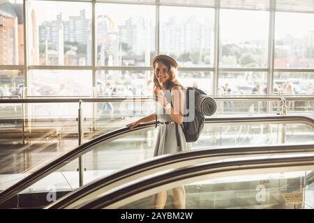 Portrait Smiling Woman Wearing Hat In Airport At Escalator. people traveling with hand luggage. Theme tourism and transport. Cau - Stock Photo