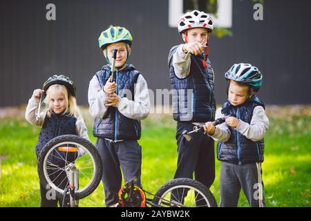 Children mechanics, bicycle repair. Happy kids fixing bike together outdoors in sunny day. Bicycle repair concept. Teamwork fami - Stock Photo