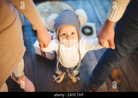 Funny little baby boy 1 year old learning walk home in winter in a decorated New Year house. Young family dad and mom hold by th - Stock Photo