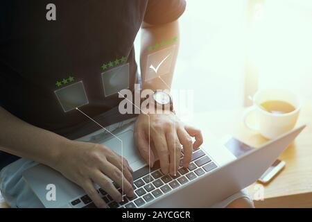 Businessman pressing rating or ranking choice on the keyboard - Stock Photo
