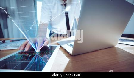 Businessman using laptop and digital tablet to analyse sales report - Stock Photo