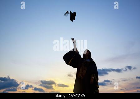 Silhouette Of Young Female Student Celebrating Graduation
