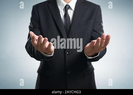 Businessman  in black suit lending a helping hand