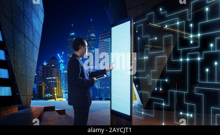 Smart businessman touch the screen to search the information of intelligent communication network of things . Night scene with m - Stock Photo