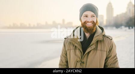 Close-up Caucasian young male red hair and beard in a hat and a park coat posing winter model against a background of a lake to