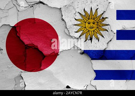 flags of Japan and Uruguay painted on cracked wall - Stock Photo