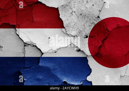 flags of Netherlands and Japan painted on cracked wall - Stock Photo