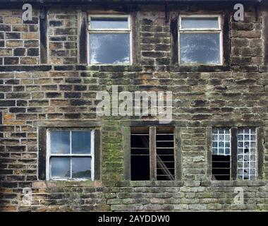 broken windows in an old derelict stone house - Stock Photo