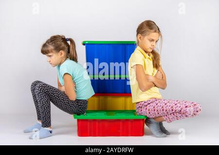 Two girls quarreled, sit on a box and turned away from each other - Stock Photo