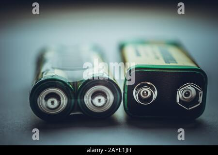 Two different types of batteries on the dark table close-up - Stock Photo