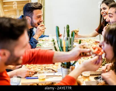 Group of happy friends eating home delivery pizza at home - Young trendy students having fun laughing together at dinner - Focus on top left man face - Stock Photo