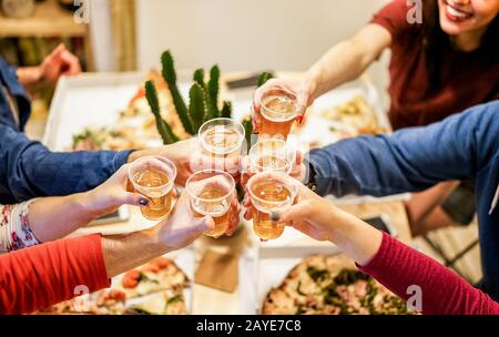Group of happy friends cheering at home with beer - Young people having fun together eating italian pizza take away - Dinner,party and friendship conc