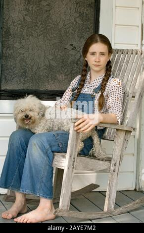 A young, bare-footed girl wearing overalls with freckles and pigtails, sitting on the front porch in an old rocking chair, with a little Bichon dog. - Stock Photo