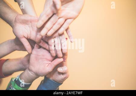 Close up bottom view of young people putting their hands together - Friends with stack of hands showing unity and teamwork - Focus on two bottom hands - Stock Photo
