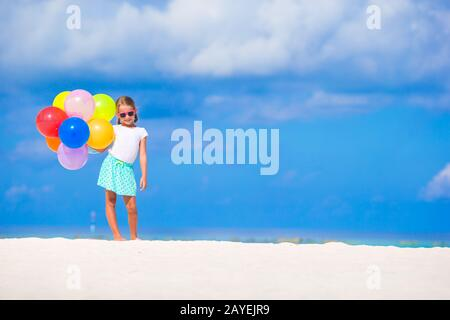 Adorable little girl playing with balloons at the beach - Stock Photo
