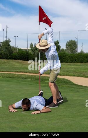 Vertical photo of a boy with a hat playing with a flag on a golf course with a man lying on the ground next to a hole - Stock Photo