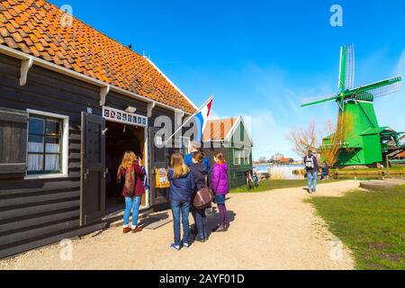 Zaanse schans, Netherlands - April 1, 2016: Green colorful dutch windmill in traditional village, tourists, blue sky in North Holland - Stock Photo