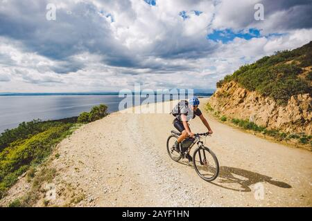 young guy riding a mountain bike on a bicycle route in Spain. Athlete on a mountain bike rides off-road against the background o