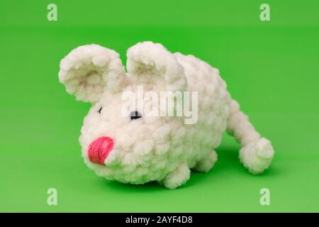 White knitted mouse, made with its own hands, on a green background - Stock Photo