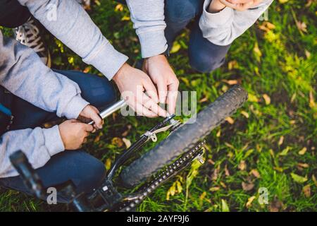 Father day. A large friendly family father and sons together actively relax in the fresh air. Dad teaches sons to repair bicycle - Stock Photo
