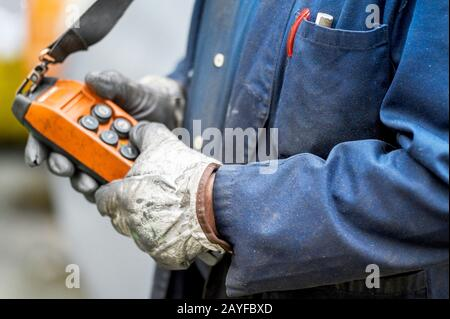 Male hand push remote control switch for overhead crane in the factory, close-up. Electrical control panel of the crane and other lifting equipment in laborer hand .