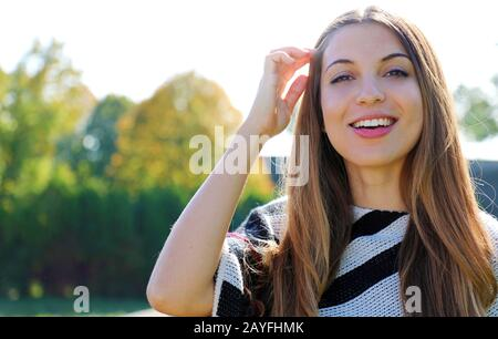 Close up of young smiling woman outdoor looking at camera in spring - Stock Photo