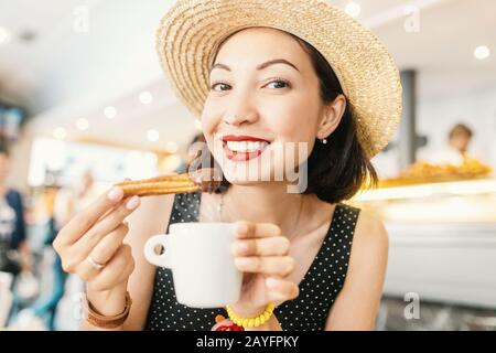 Happy Cheerful girl in hat eating traditional spanish delicious churros, a fried pastry with chocolate in cafe in spain - Stock Photo