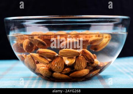 Almonds kept in a glass bowl containing water. Peeling of almond skin in progress - Stock Photo